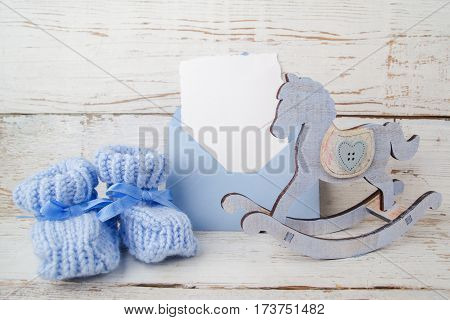 Blue booties for the baby on a wooden background and wooden horse.