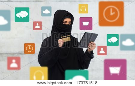 finances, technology, online shopping and people concept - muslim woman in hijab with tablet pc computer credit card over gray concrete wall background