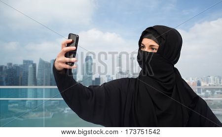 technology and people concept - muslim woman in hijab taking selfie with smartphone over singapore city skyscrapers background