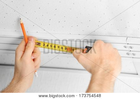 Male hands making curtain rail measurements