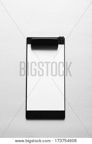 Black plastic clipboard on light background