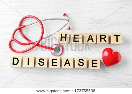 Text HEART DISEASE made of cubes and stethoscope on wooden background