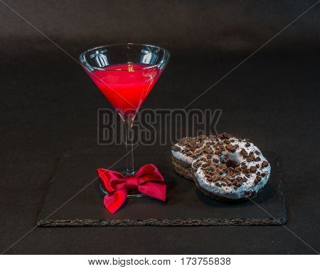 drink cosmopolitan a glass of martini decorated with a red bow with two oreo doughnut on a black stone plate the party set