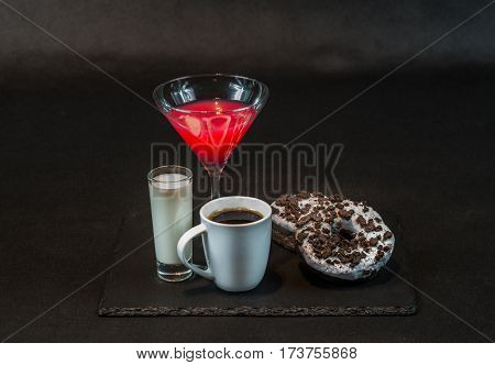 drink cosmopolitan a glass of martini  with coconut liqueur in a glass with coffee with two oreo doughnut on a black stone plate party set