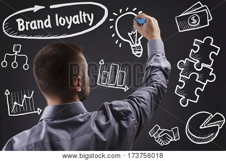 Technology, Internet, Business And Marketing. Young Business Man Writing Word: Brand Loyalty
