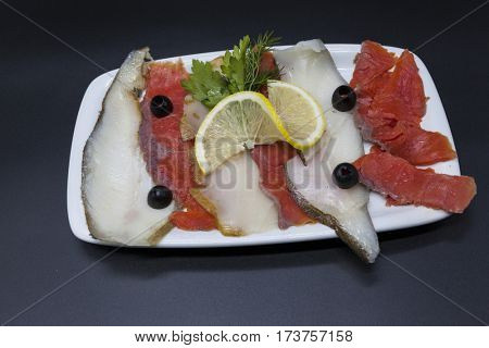Smoked fish, Delicacies from the Northern seas halibut, salmon.Slices of smoked salmon and halibut on a plate with a slice of lemon and olives