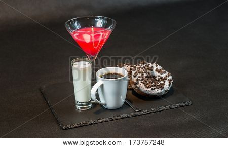 left side view on a drink cosmopolitan a glass of martini decorated with a red bow with coconut liqueur in a glass with coffee with two oreo doughnut on a black stone plate party set