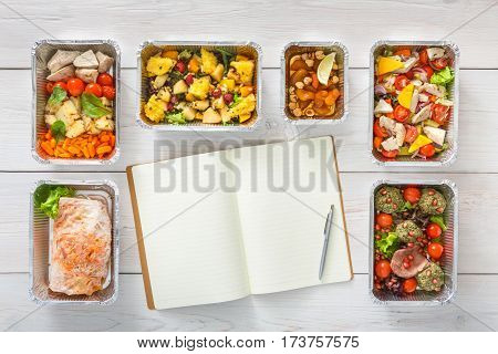 Diet plan mockup with healthy restaurant food delivery. Natural organic fitness nutrition for diet. Daily meals in foil boxes with copy space at white wood. Top view, flat lay