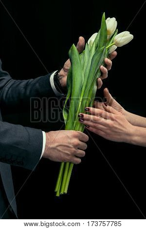 Partial view of man presenting tulips to woman on black international women's day concept
