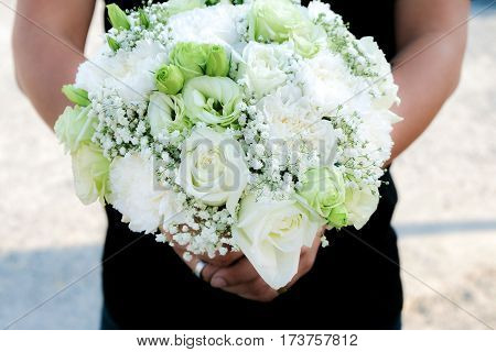 Bouquet of white roses in hand a young man preparing to deliver a lover on Valentine's Day