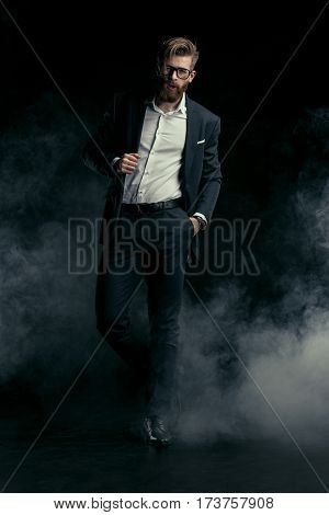 Stylish handsome bearded man in trendy suit and eyeglasses posing in smoke