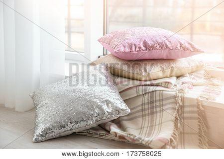 Three shiny glamorous pillows on windowsill