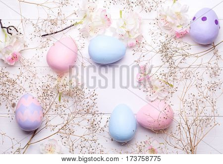 Colorful Easter eggs and flowers on paper with space for text. Top view