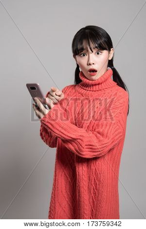 A studio portrait of a twenties Asian woman with a surprised look on the phone