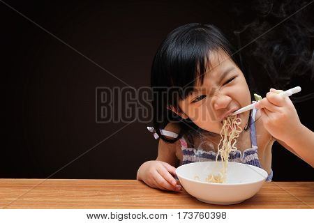 Asian child girl eating Instant noodles isolated on black background with clipping path