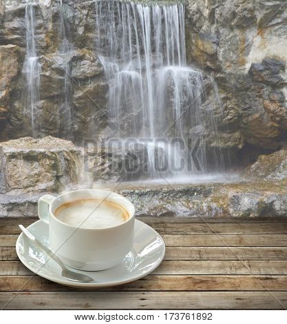 Hot coffee in white cup over wooden table with spoon on waterfall background.