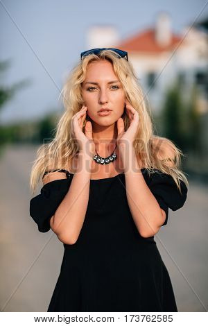 Portrait Of Beautiful Blonde Girl In Black Glasses And Black Dress Walking Down The Street.