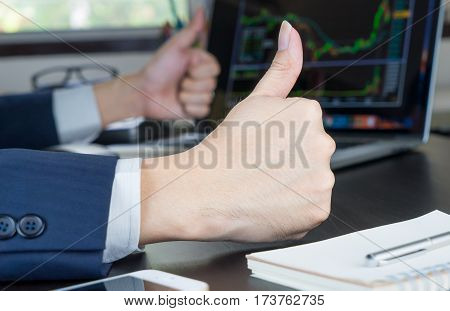 Stock trader is celebrating Thumbs up as the Stock Market is going up.