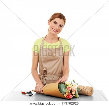 Beautiful female florist wrapping flower bouquet in paper on white background