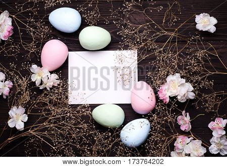 Colorful Easter eggs and flowers on paper with space for text on a dark wooden background. Top view