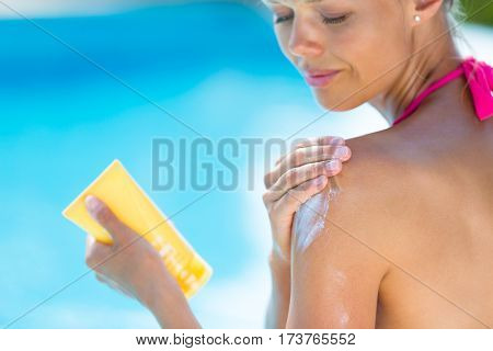 Attractive, young woman with healthy skin applying suncream by a pool (shallow DOF; color toned image)