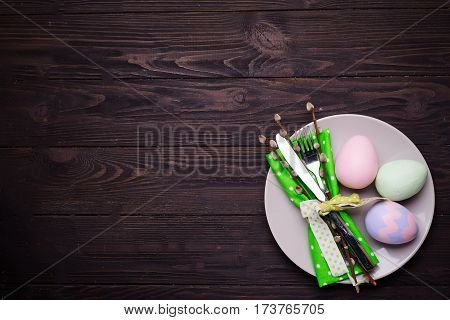 Easter table place setting with plate, cutlery and decor egg on dark wooden background, top view. Spring or Easter food concept