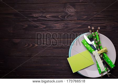 Easter table setting with cutlery on a dark wooden background with a piece of paper for your text on a plate