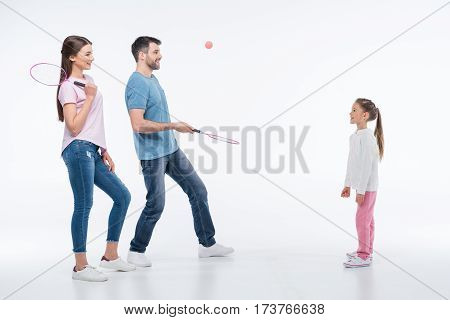 smiling family playing badminton with rackets and shuttlecock on white
