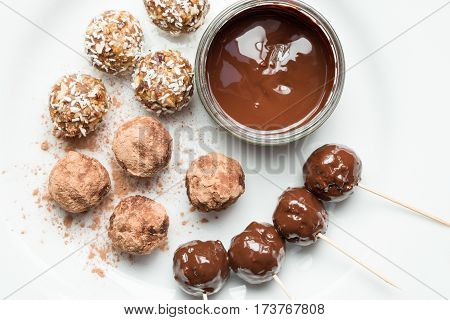Overhead Of Melted Chocolate Surrounded By Various Protein Energy Balls