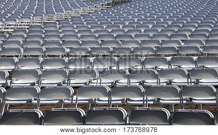 Lots of white chairs at the stadium