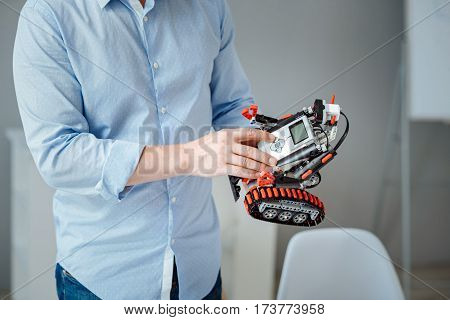 Robotic technologies. Professional engineer holding robot and using it in a lab