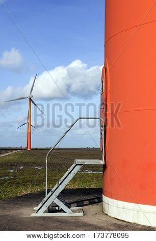 orange wind turbines in the netherlands on the island of flevoland near Almere with blue sky