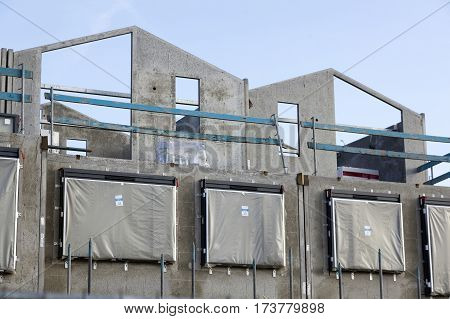 concrete frame of newly built house with scaffolding around and blue sky