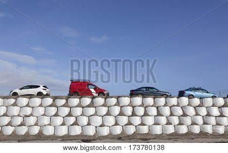 large amount of sandbags form road for cars under blue sky