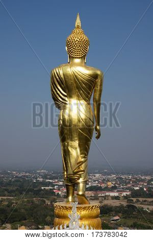 giant golden buddhist figurine on Khao Noi hill looking to Nan City