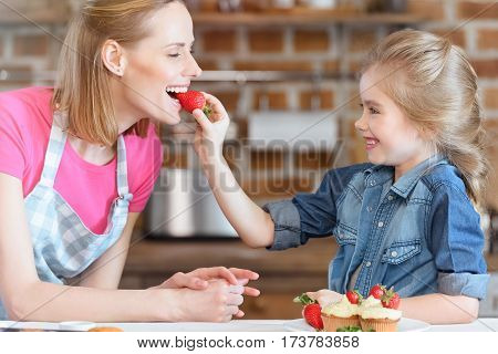 side view of daughter feeding mother with strawberry from cupcake