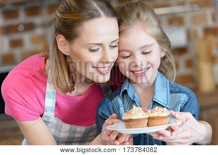 portrait of smiling mother and daughter holding plate with cupcakes