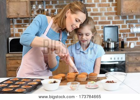 portrait of mother putting cream on cupcakes with daughter near by