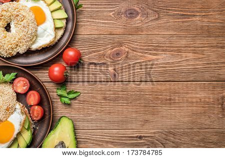 Bagel with avocado and egg on the wooden background.