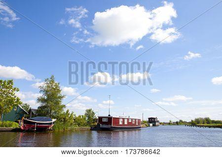 Dutch houseboats on little river in The Netherlands landscape