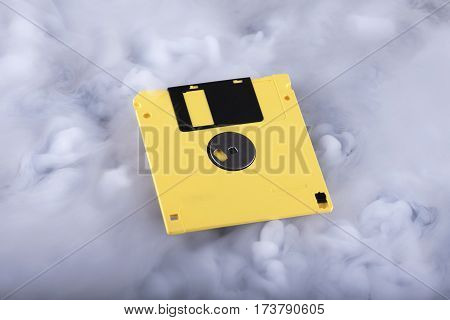 Yellow retro floppy disk in clouds. Information cloud conceptual image. Selective focus