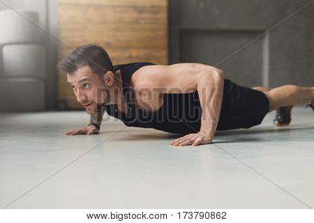 Young man workout in fitness club. Closeup portrait of caucasian guy making plank or push ups exercise, training indoors