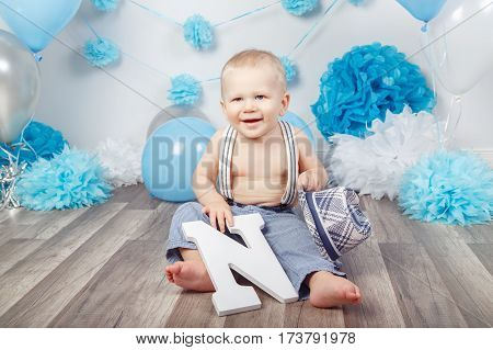 Portrait of cute adorable Caucasian baby boy with blue eyes barefoot in pants with suspenders and hat sitting on wooden floor in studio holding large letter N looking away first year concept
