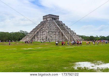 CHICHEN ITZA, MEXICO - JULY 12, 2011: Uknown people visiting Kukulkan pyramid in Chichen Itza, Yucatan. Kukulkan pyramid is one of seven New World Wonders and popular tourist destination in Mexico.