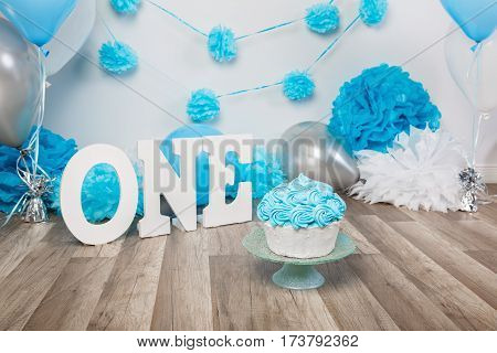 Festive background decoration for birthday celebration with gourmet cake letters saying one and blue balloons in studio cake smash first year concept
