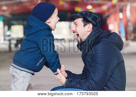 Portrait of smiling laughing white Caucasian father and son talking to each other happy family of two lifestyle outside on a spring autumn day