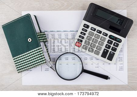 Electronic Calculator, Magnifying Glass And Notepad With Pen On Printout