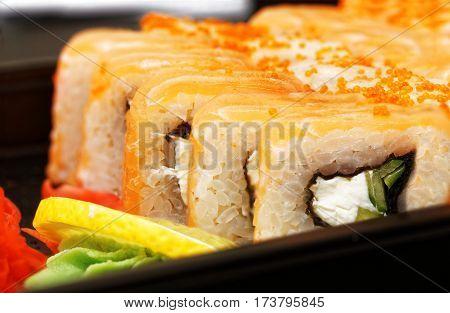 Closeup fresh maki sushi with gari ginger wasabi and lemon on black plate. Shallow focus.