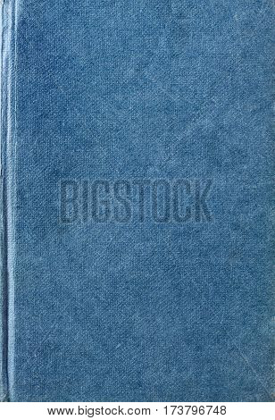 Texture background of an old scratched lightly worn and marked blue fabric woven book cover.