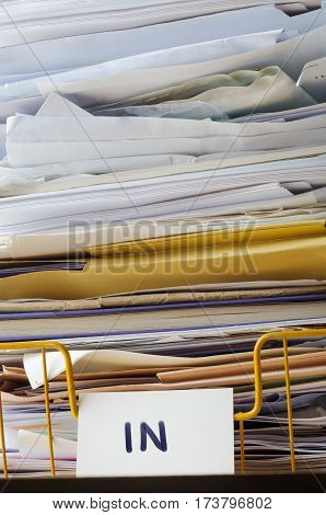 A wire office tray labeled 'In' piled high with papers documents and folders that reach to the top of the frame and extending beyond it.